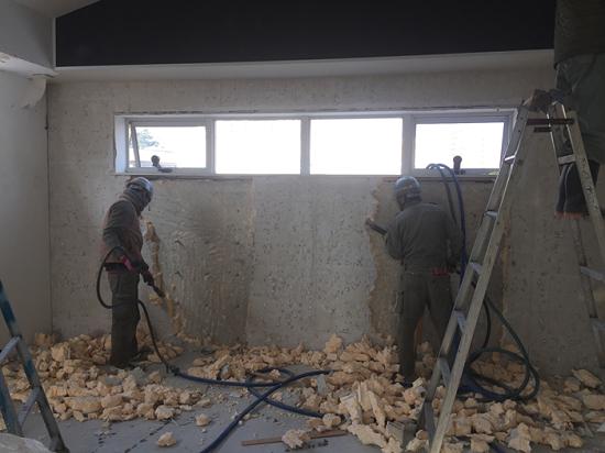 リサイクルのため、コンクリートと完全密着した断熱材をはがしています