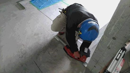 内部間仕切りの上下に使用する「ランナー」を床に留め付けているところ