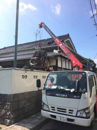 ユニック車(クレーンを搭載した型のトラック)で機材を吊って敷地内に運び入れます