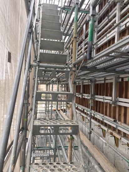 階上に上がるには外部足場に設けられた仮設階段を利用