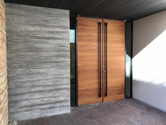 両開きの玄関扉と杉板型枠で造られたコンクリート打ちっぱなしの壁
