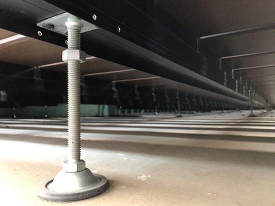 防水層の上に束を立てて架台を組み、高さを調整してウッドデッキを敷込